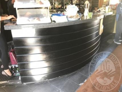 Bancone bar rivestito in legno di colore nero, piano di servizio in metriale tipo marmo, piano di lavoro in acciaio, completo di lavabo, cassetti e celle refrigerate